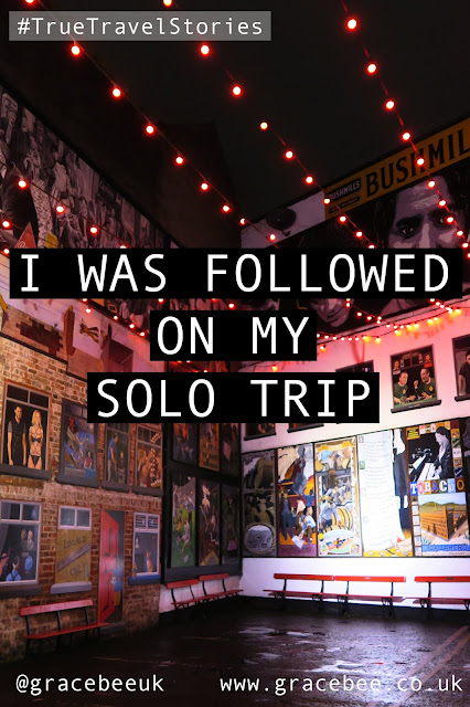 """An image showing a courtyard walls which are full of murals. Text over the image reads """"I was followed on my solo trip"""""""