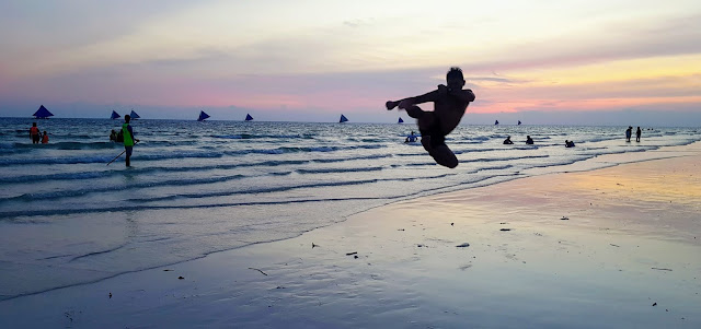 Sun-down silhouettes: a mid-air taekwondo kick, a paddle boat instructor, last-light beach-bathers; last-trip paraw sails || GREGG YAN