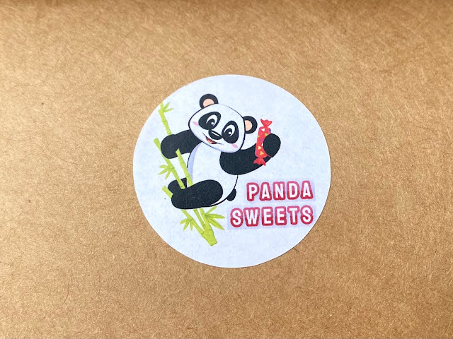 The Panda Sweets logo on a sticker on a brown cardboard box