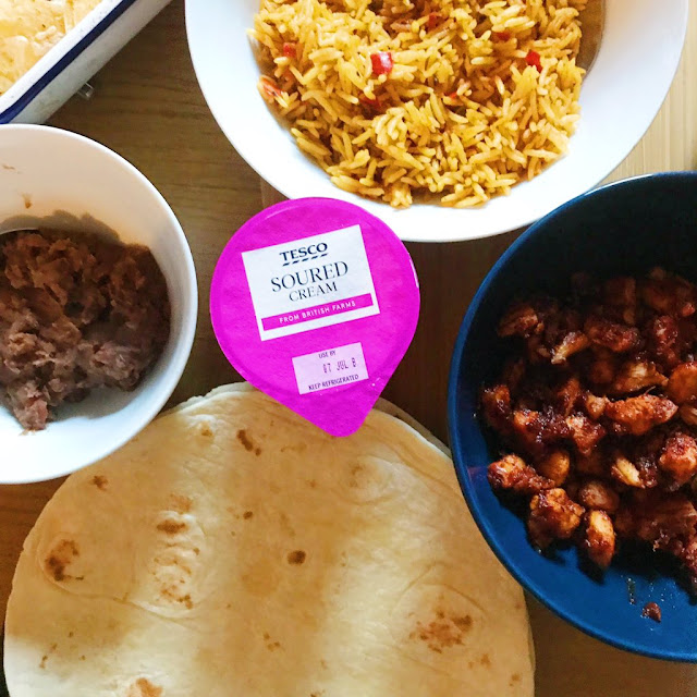 flatlay of food closeup - refried beans, golden rice, sour cream and chicken