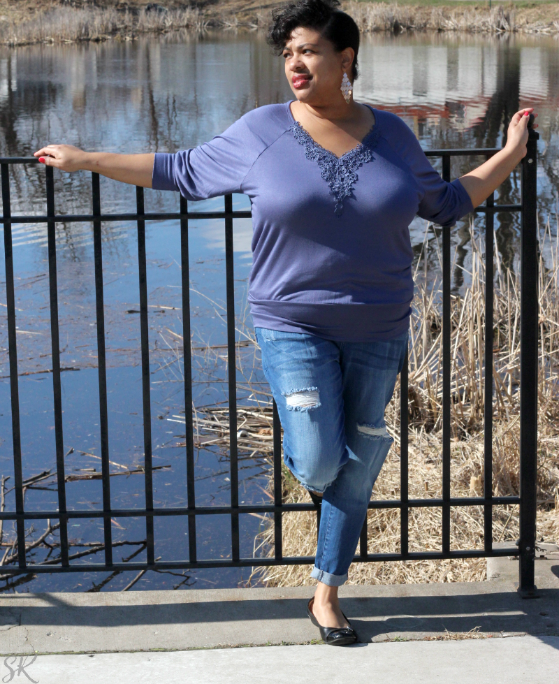 a woman standing next to a pond posing in a blue outfit