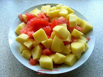 Πατάτες ξεφλουδισμένες και κομμένες σε κομμάτια και ντομάτες κομμένες σε κύβους ετοιμα μέσα σε πιάτο για την παρασκευή της συνταγής