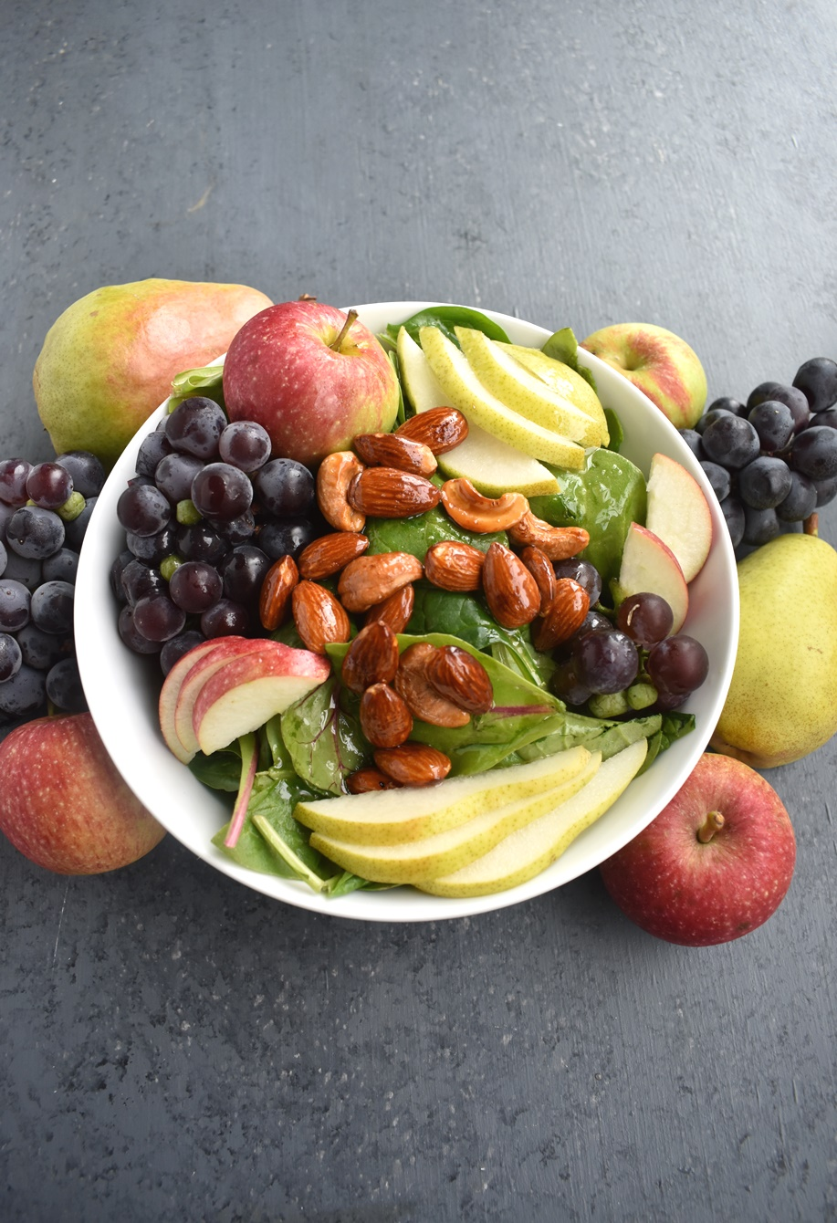 Harvest Salad with Apple Cider Vinaigrette is loaded with the season's best grapes, pears and apples along with honey candied almonds and cashews! #salad #healthy #cleaneating #fall #fallfood #harvest #apples #grapes #pears #nuts