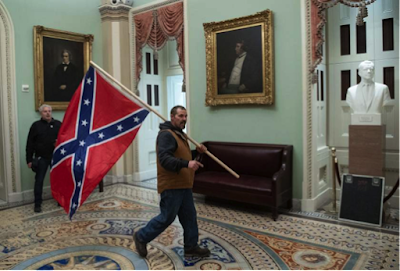 Man holds Confederate battle flag, walks through room with portraits and sculpture