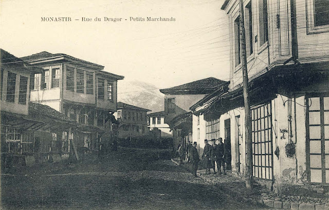 Street near the river Dragor. In the background is seen the peak Pelister. In the ground floors of these houses on both sides of the street are small shops and bakery on the left side. On this picture is visible telephone pole and wires that go across the street.