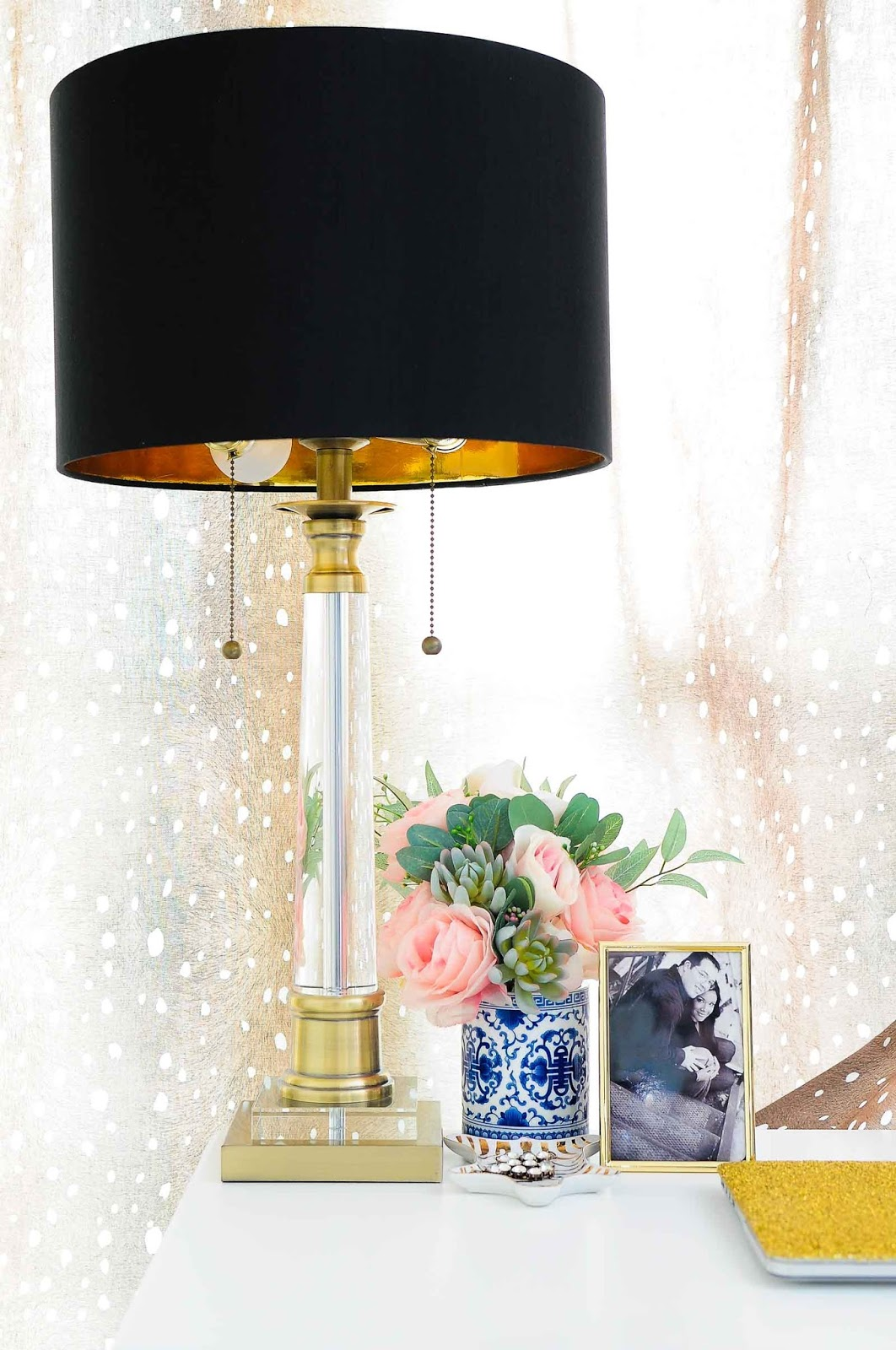 Brass and crystal lamp in a feminine home office with fawn curtains.