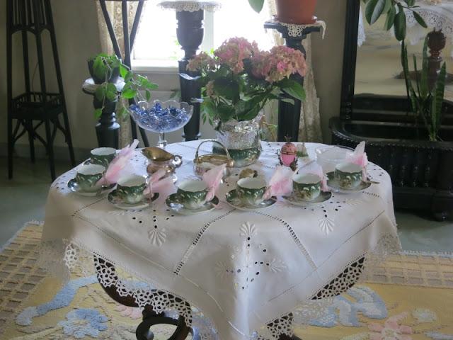 Pöydän päällä on valkoinen päytäliina. Pöydällä on kahvikuppeja ja pääsiäisasetelma.