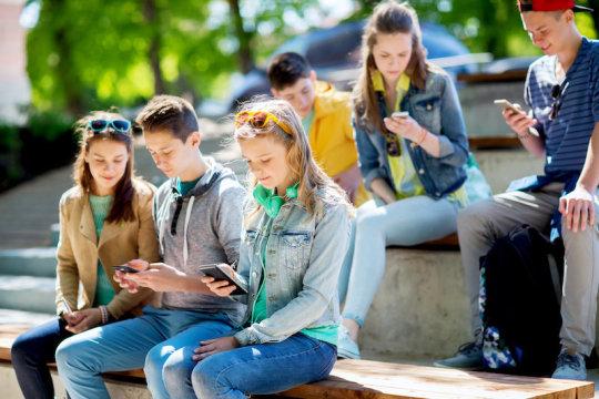 مراهقين يستخدمون الهواتف الذكية