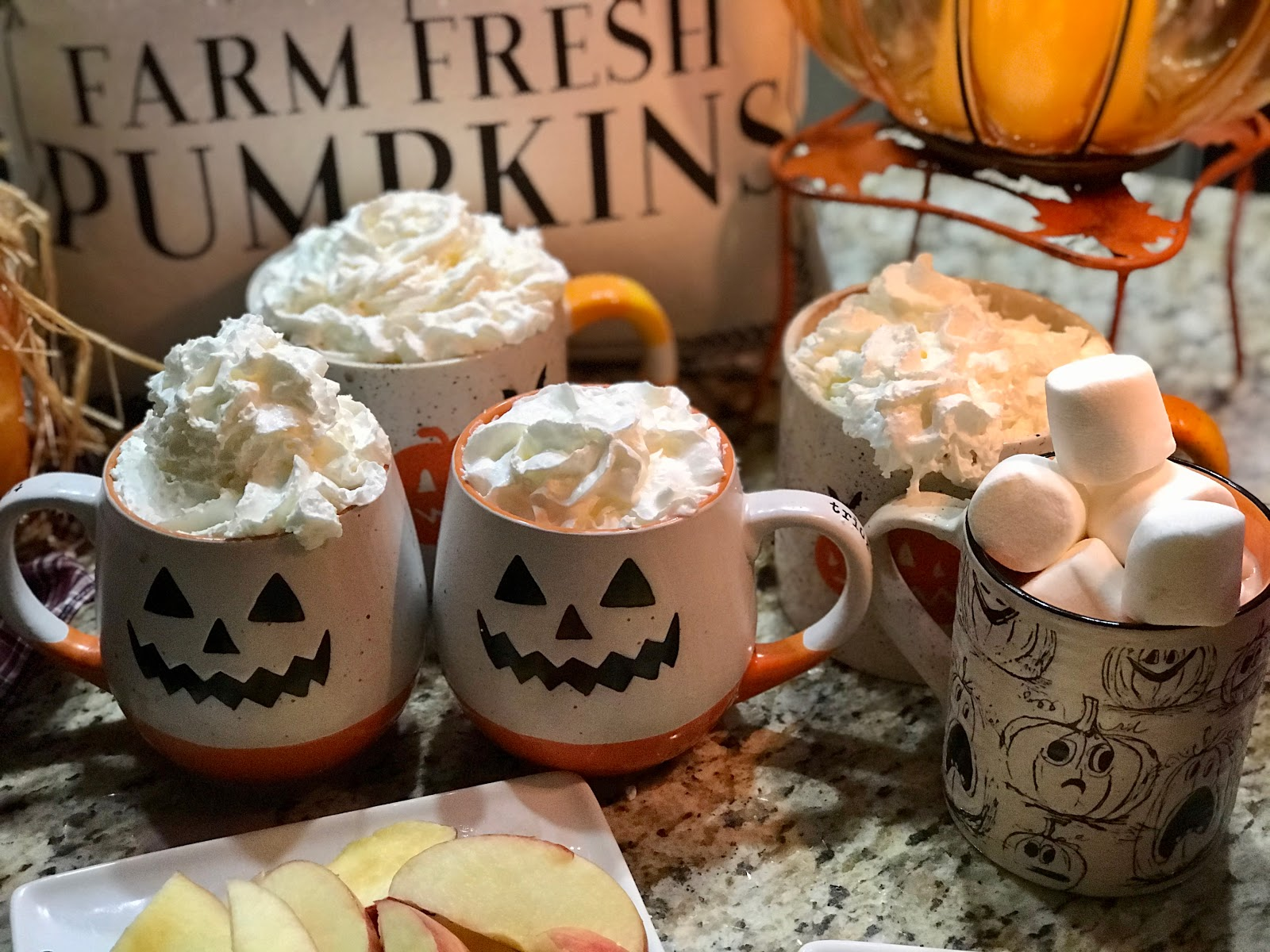 Spooky cups filled with hot cooca whip cream and marshmellows