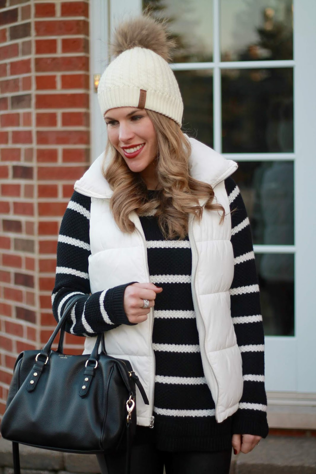 black and white striped tunic sweater, white puffer vest, white fur pom beanie, spanx leather leggings, black leather western bootie, kate spade cross body