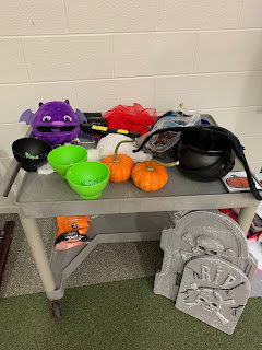cart with 3 bowls of green slime, purple monster, yellow eyes tube, red scarves, blue wizard puppet, bubble wands, black cauldron with black bat inside, 2 pumpkins, and 2 foam tombstones leaning on cart