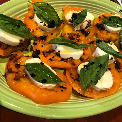 large slices of yellow tomato topped with slices of basil and a single basil leaf, dotted with balsamic vinegar