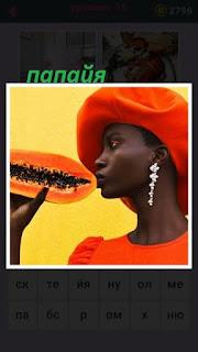 девушка в оранжевом платье хочет есть папайя оранжевого цвета