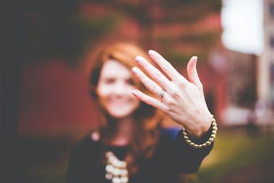 Mujer enseñando su alianza y su anillo de compromiso