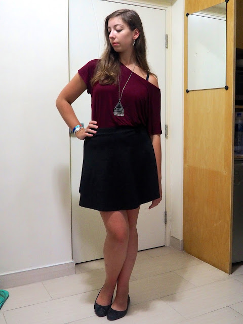 Inverted | outfit of loose off-the-shoulder burgundy red top, short black skater skirt, and flat black ballet pumps