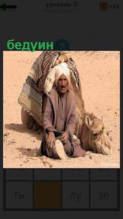 На песке в пустыне сидит бедуин с верблюдом в чалме на голове