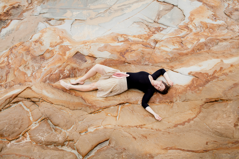 girl lying on rock with wooden vulva