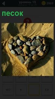 Камни уложены в песок в форме сердца символизирующее любовь мужчины и женщины