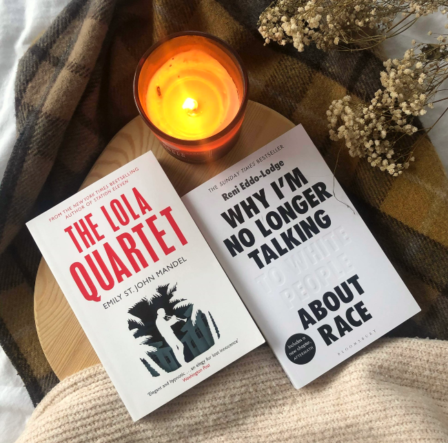 Front covers of The Lola Quartet and Why I'm No Longer Talking to White People About Race. Sat next to each other by a candle