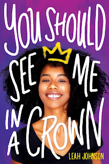 A Black girl in a black v-neck shirt and her hair framing her face is smiling with a cartoon of a yellow crown perched on top of her head.