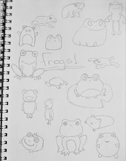 """Sketch book with """"frogs"""" written in the middle with pencil drawings of different frog designs"""