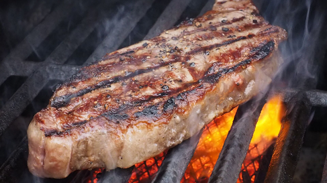 a long steak on the grill with flames beneath