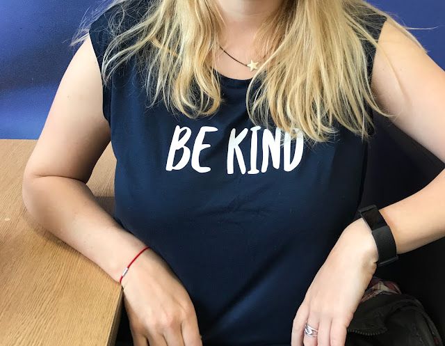 "A body shot of me wearing a navy tank t-shirt with the words ""BE KIND"" written in white"