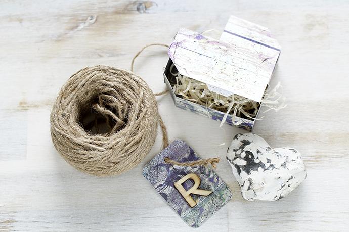 """Rolle mit Paketschnur, Schachtel mit Holzwolle und Etikett aus Papier mit einem kleinen """"R"""""""