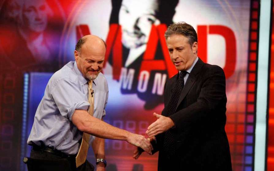 Jon Stewart gesturing to Jim Cramer to have a seat as they shake hands