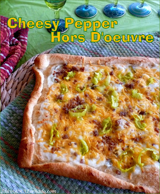 A perfect appetizer for the holiday season, Cheesy Pepper Hors D'oeuvre layers pepper jelly cream cheese with sharp cheddar, pepperoncini and bacon bits. | Recipe developed by www.BakingInATornado.com | #recipe #appetizer