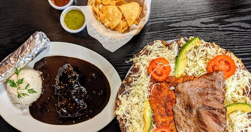Chips, mole negro, and a tlayuda are served