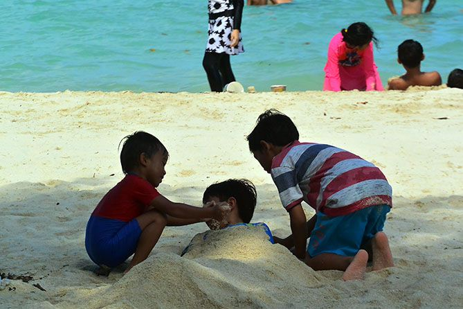 Anak kecil bermain pasir pantai