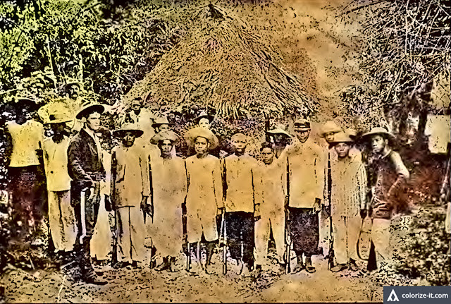 "Captured Filipino ""insurgents"" with American soldiers during the Philippine-American War. Image extracted from the public domain book ""Souvenir of the 8th Army Corps Philippine Expedition:  a Pictorial History."" Colorized courtesy of Algorithmia."