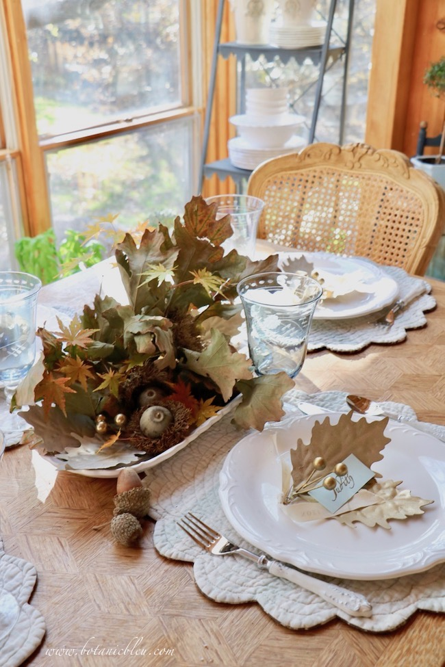Thanksgiving Natural Centerpiece tips for using twigs, leaves, and acorns show a few acorns lying outside the centerpiece