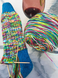 hand knit socks of rainbow variegated yarn and blue cuffs and heels