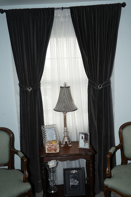 Antique table, gray velvet curtains with swanky tie backs