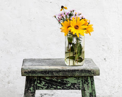 Glass vase of flowers on a stool