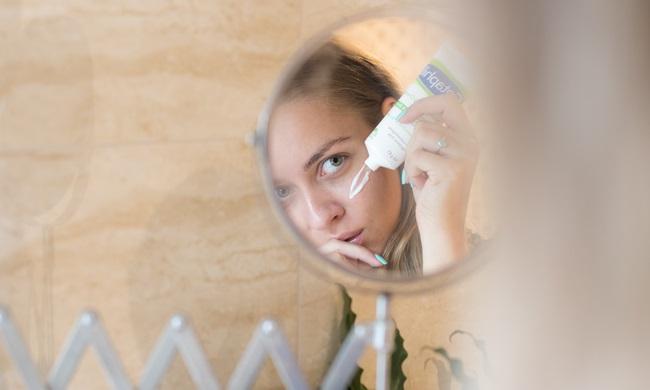 Mulher ao espelho passando um creme