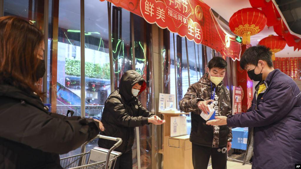 Un empleado distribuye desinfectante a clientes a la entrada de un supermercado en Wuhan, en la provincia de Hubei, en el centro de China, el sábado 25 de enero de 2020, debido a una epidemia de un mortal virus que afecta las vías respiratorias / AP