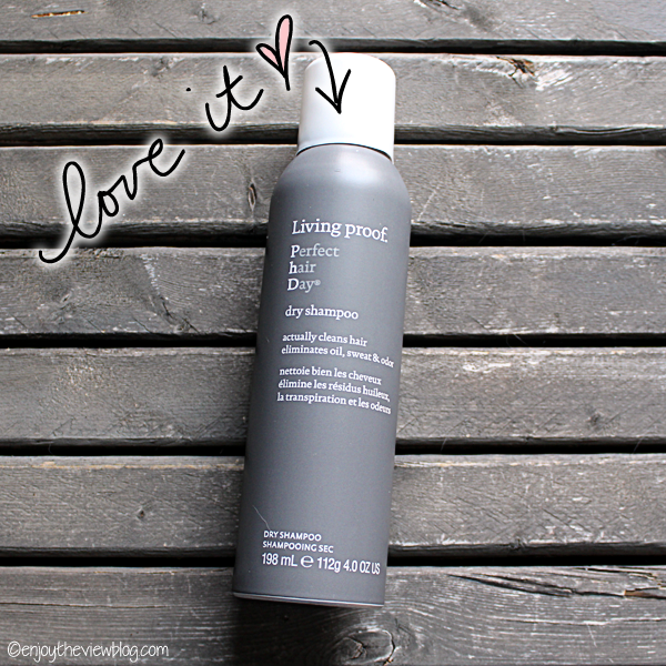 "Bottle of Living Proof Dry Shampoo lying on a wooden table with the words ""love it"""