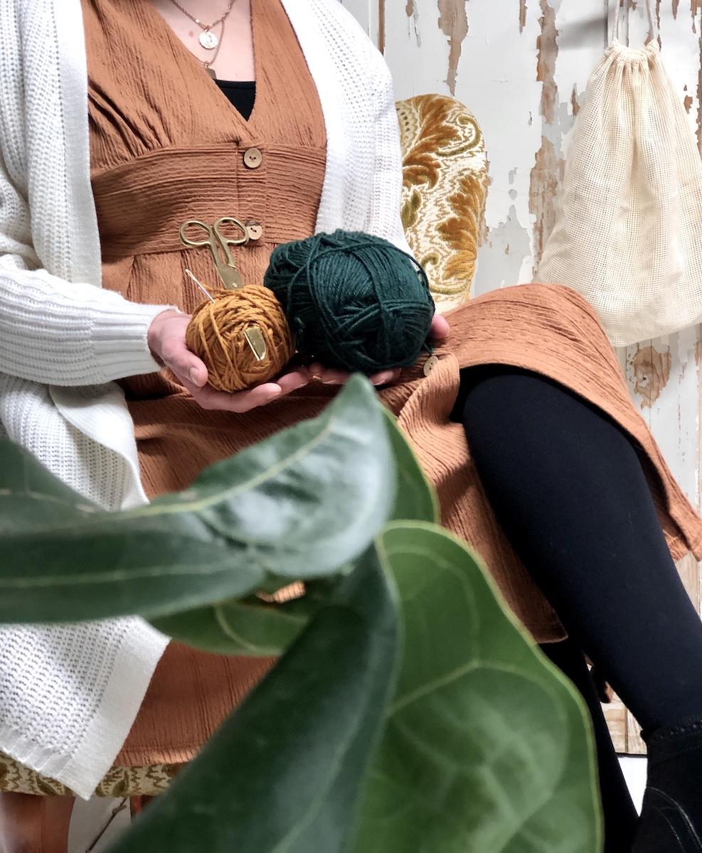 Kasvin takaa kuvattu istuva nainen, jolla käsissään kaksi lankarullaa. Takana vanha ovi jonka kahvasta roikkuu vaalea kestohedelmäpussi.