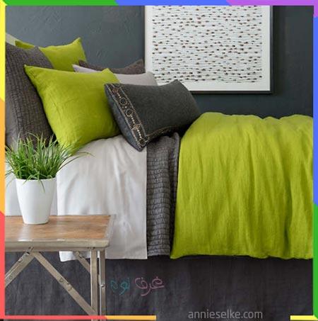 سرير نوم مع بطانية باللون التفاحي داخل غرفة نوم رمادية