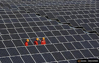 Workers walk among newly installed solar panels at a solar power plant in the Zhouquan township of Tongxiang, Zhejiang province. (Credit: Reuters) Click to Enlarge.