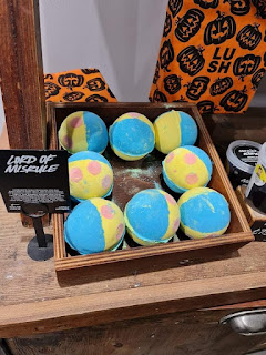 A large light brown square box filled with yellow and green jester inspired design bath spherical bath bombs with a black card saying lord go misrule in white font on a bright background