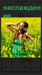 наслаждение девушки в наушниках, стоящей в поле среди цветов