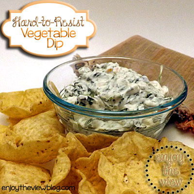 vegetable dip in a glass bowl surrounded by tortilla chips
