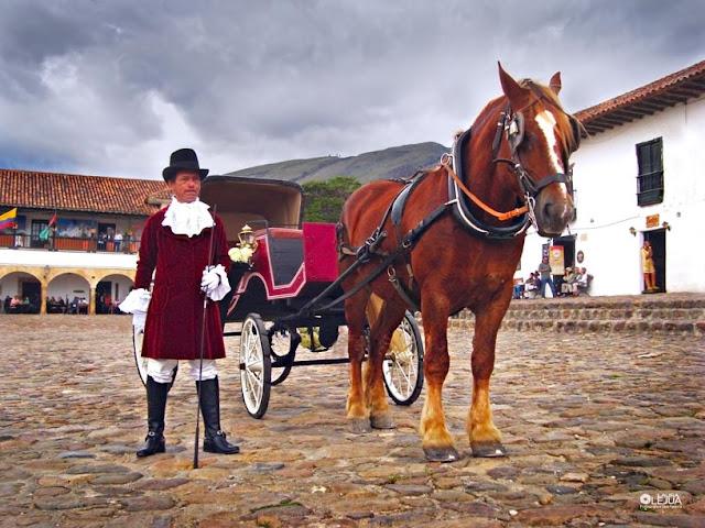 Carruaje, caballo y jinete en la plaza principal de Villa de Leyva
