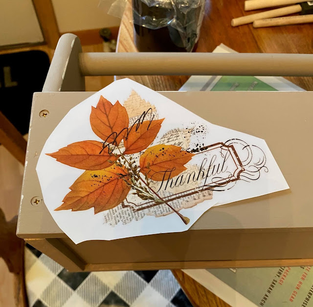 Photo of a fall decor transfer being positioned on a toolbox.