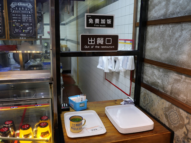 """免费加饭 - Free meals"" sign at a restaurant"