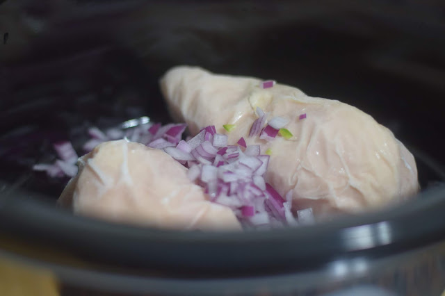 Diced onion added to slow cooker with the chicken.